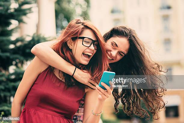 Two friends texting outdoor