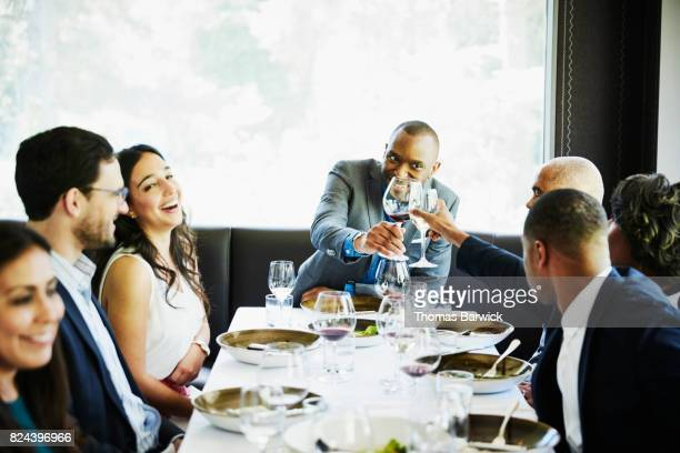 Two friends toasting while dining with family and friends in restaurant