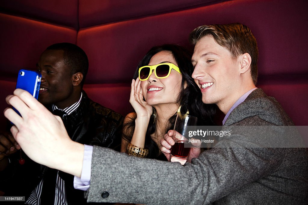 Two friends using a cell phone to take a picture. : Stock Photo