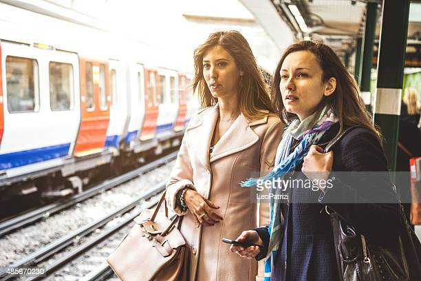 Two friends waiting for the train in the subway platform