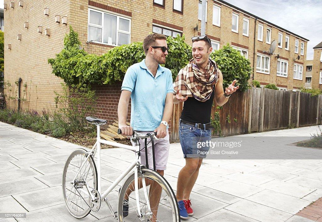 two friends walking down the street, talking : Stock Photo
