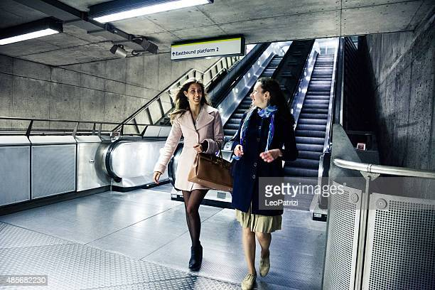 Two friends walking down to take the subway train