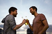 Two friends with beer bottles outdoors