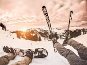 Two friends with snowboard an ski watching the sunset on snow high mountains - Young athlete having fun on white week - Winter extreme sport, adventure, travel and vacation concept - Focus on feet