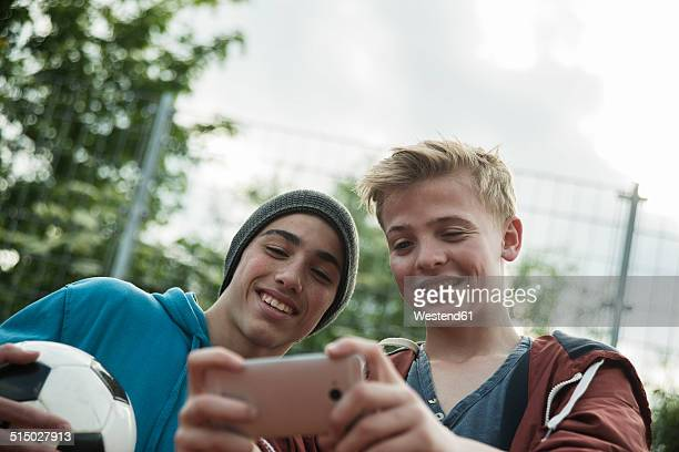 Two friends with soccer ball looking at cell phone