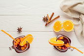 Two fruit tea in vintage glass jars with drinking straw on white wooden  background top view. Vintage jars with ice hibiscus tea, orange, cinnamon and star anise on white table, flat lay.