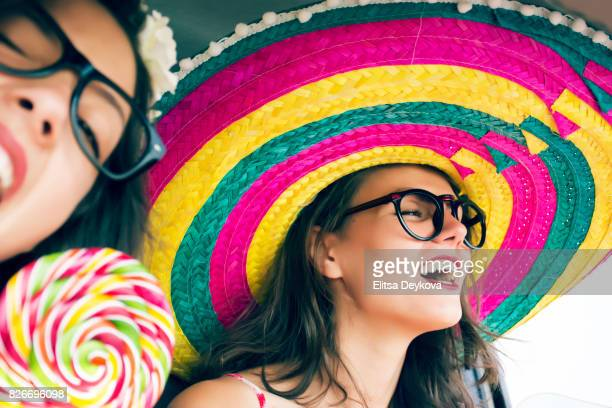 Two funny cheerful hipster women traveling in car