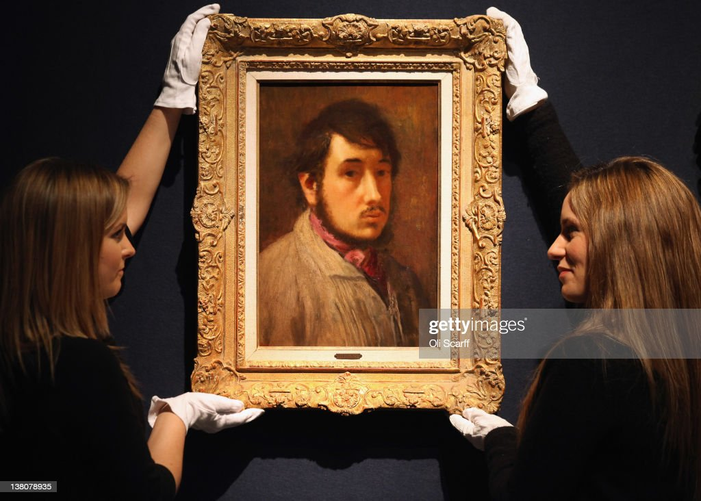 Two gallery assistants at Christie's auction house adjust a painting by Edgar Degas entitled 'Autoportrait' which was formerly owned by Elizabeth Taylor on February 2, 2012 in London, England. The artwork, which is estimated to fetch 450,000 GBP, is being auctioned in Christie's forthcoming evening sales of 'Impressionist and Modern Art' and 'Art of the Surreal' which will take place between February 7, 2012 and February 9, 2012.