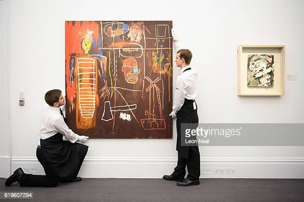 Two gallery assistants pose with 'Air Power' by JeanMichel Basquiat and 'Head of Gerda Boehm' by Frank Auerbach during the press preview of the...