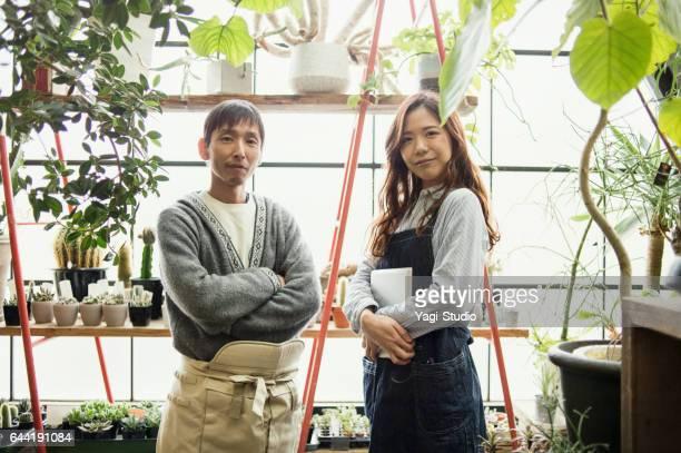 Two gardeners working in green shop.
