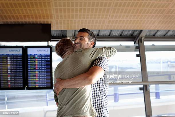 Two gay men embracing at airport
