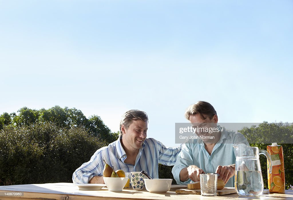 Two gay men having breakfast together outside : Stock Photo