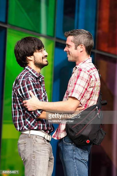 Two gay men looking at each other urban setting vertical