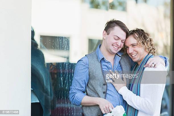 Two gay men shopping, hugging