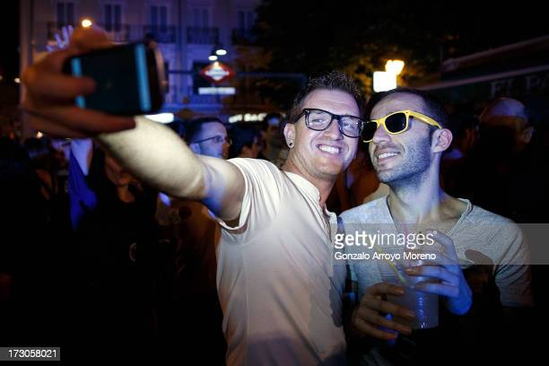 Two gay men take a picture of themselves at the Chueca Square stage during the Madrid Gay Pride Festival 2013 on July 5 2013 in Madrid Spain...