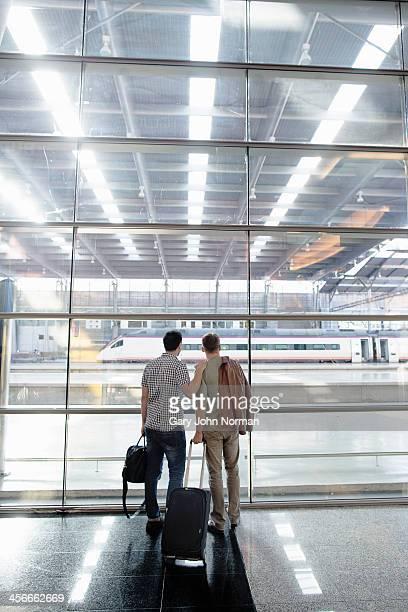 Two gay men waiting at train station