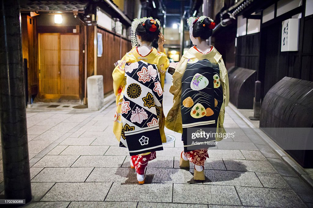 Two Geishas walking together at night.