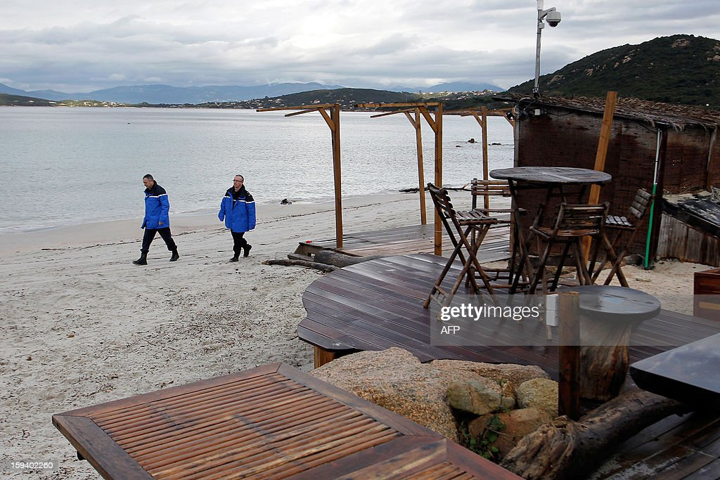 Two gendarmes walk on January 13, 2013 past the 'Beach Hut of the Silver Beach' restaurant in Porticcio. The South Corsica prefecture has ordered beach hut owners to demolish the parts that are located on the public property before January 15. If not respected the prefecture will conduct the demolition itself.