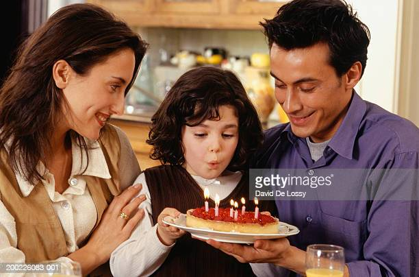 Two generation family celebrating birthday of daughter (6-7), daughter blowing out candles, waist up