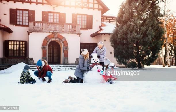 Zwei-Generationen-Familie macht einen Schneemann