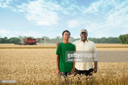 Two generations of Black farmers in wheat field