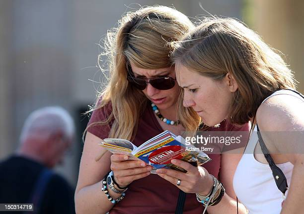 Two German tourists try to find Checkpoint Charlie on a map on August 15 2012 in Berlin Germany In 2010 nine million tourists visited the German...
