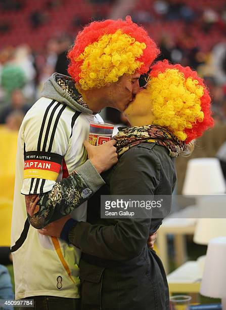 Two Germany fans kiss as they arrive to watch the GermanyGhana World Cup match at a public viewing at the Alte Foersterei FC Union stadium on June 21...