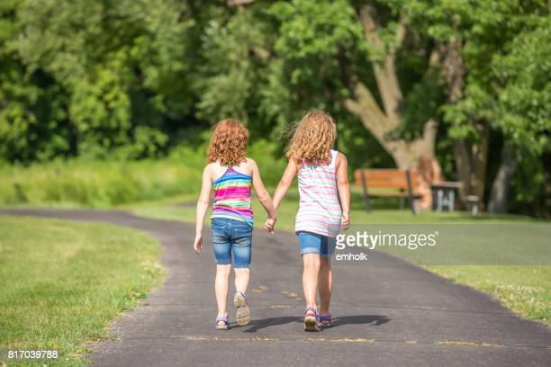 Two Girl Walking on Paved Park Trail