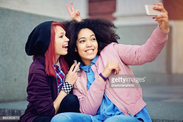 Two girlfriends are joking and taking selfie