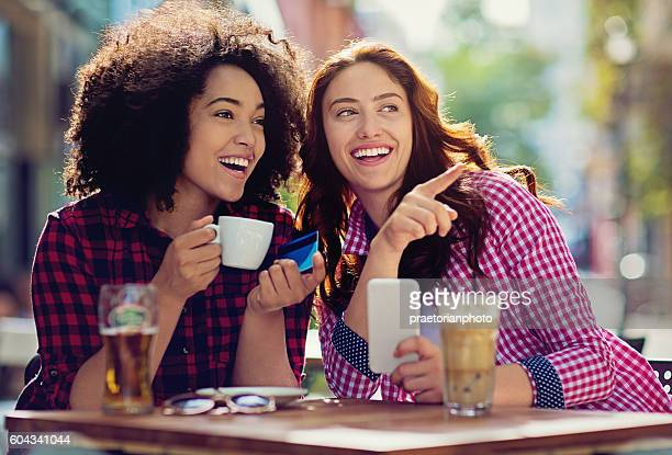 Two girlfriends are making fun in the cafeteria