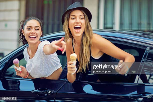 Two girlfriends are showing out the window of their car and make fun together