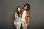 Multiethnic friendship and support concept. Diverse girls hugging and having fun at gray studio background with copy space