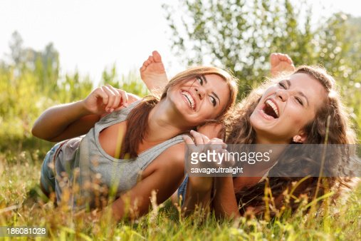 two girlfriends lying down on grass : Stock Photo
