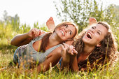two girlfriends in T-shirts  lying down on grass laughing having good time