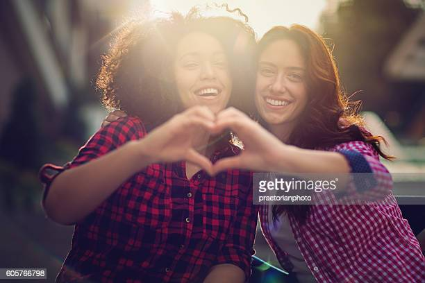 Two girlfriends making heart with their hands