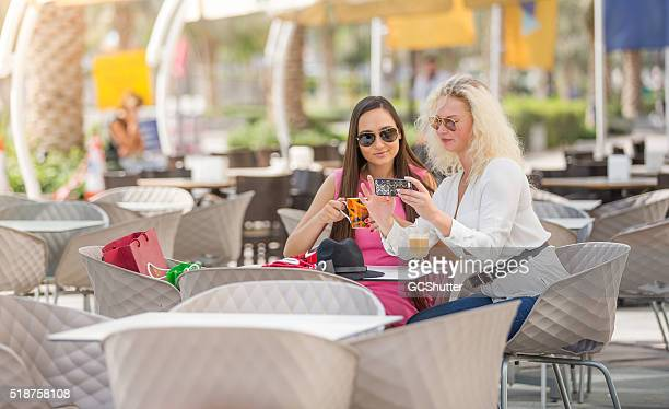 Two Girlfriends playing with their phone at an Outdoor Cafe