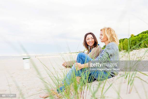 Two girlfriends relaxing on sandy beach