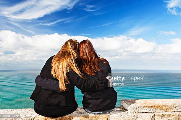 Two girlfriends sit on clifftop wall overlooking ocean, embracing affectionately