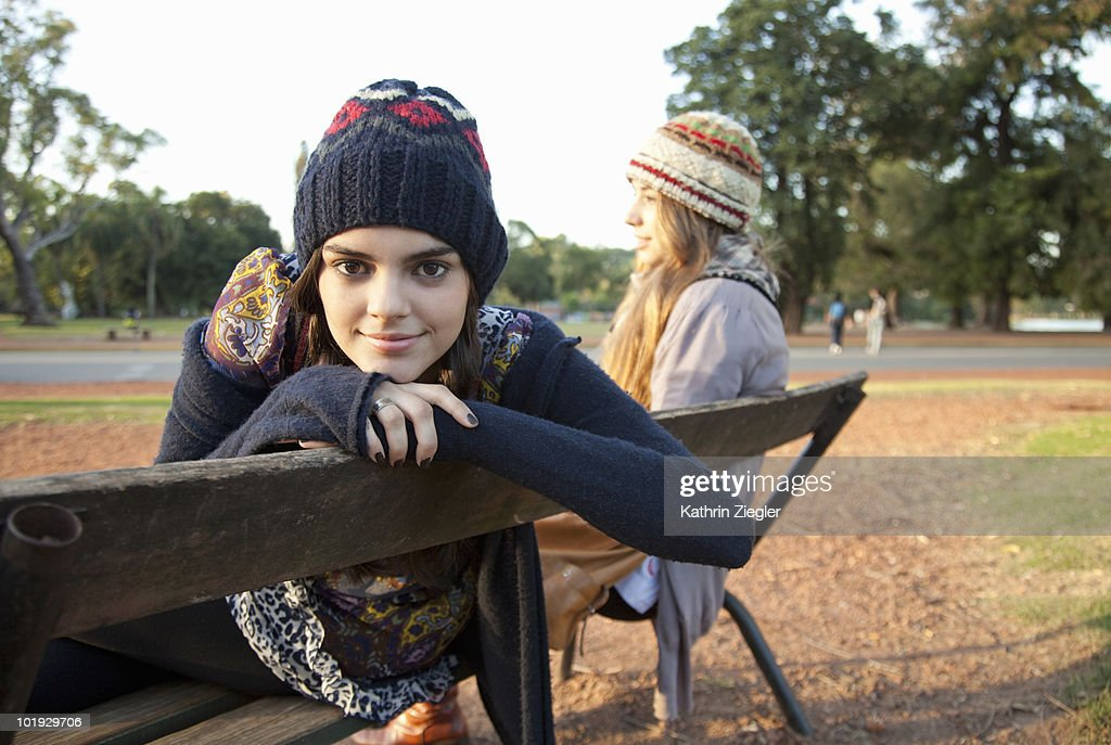 two girlfriends sitting on a bench in the park : Stock Photo