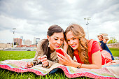 Two girlfriends using a phone at an urban park