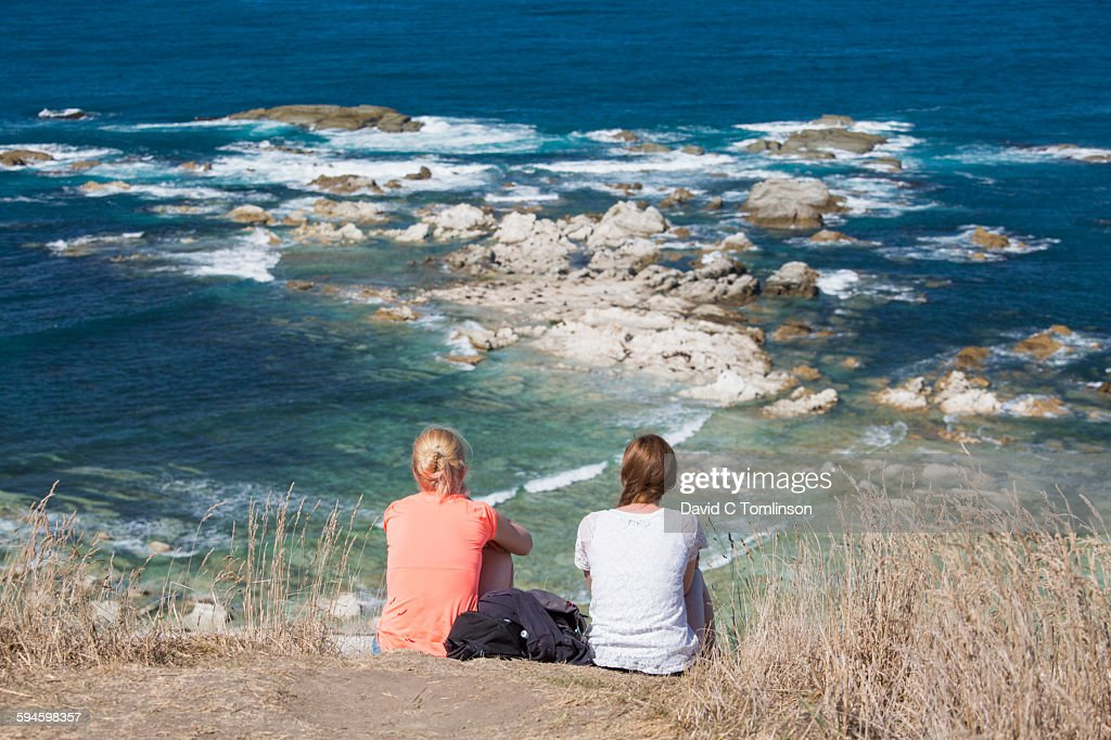Two girls admiring view from cliff edge, Kaikoura