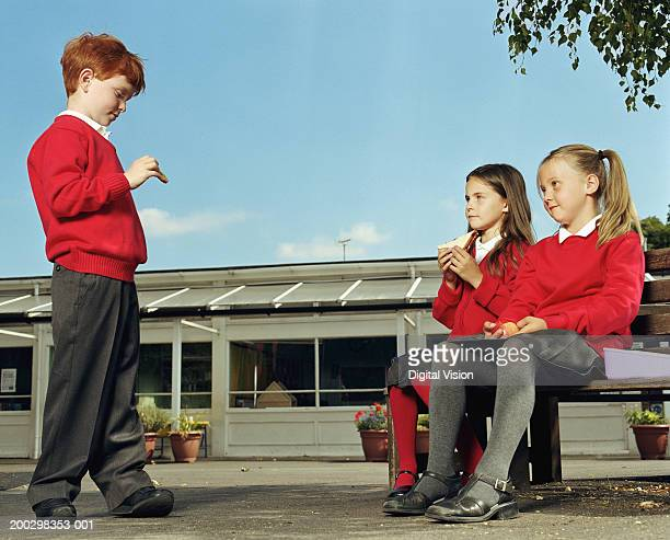 Two girls (6-8) and boy (5-7) eating lunch in playground