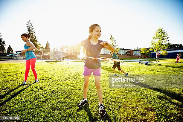 Two girls and boy hula hooping on field