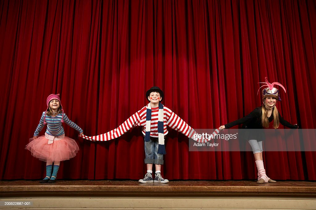 Two girls and boy (6-10) in costume taking bow on stage, smiling