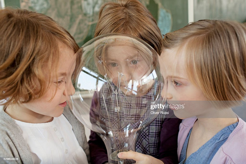 Two girls (6-7) and boy (8-9) looking at large light bulb : Stock Photo