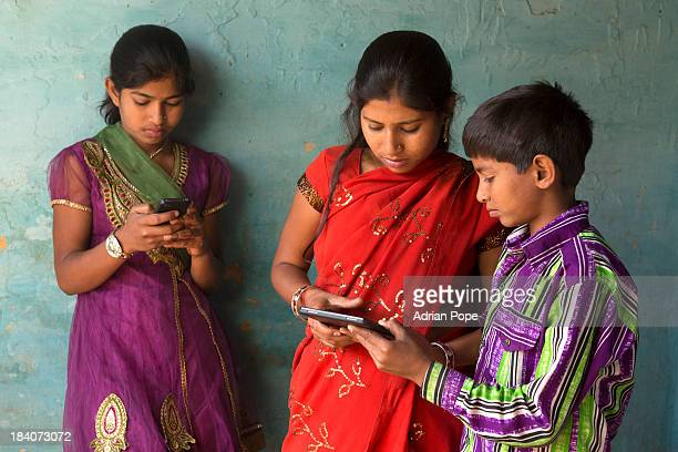 Two girls and boy using smartphone and tablet devi