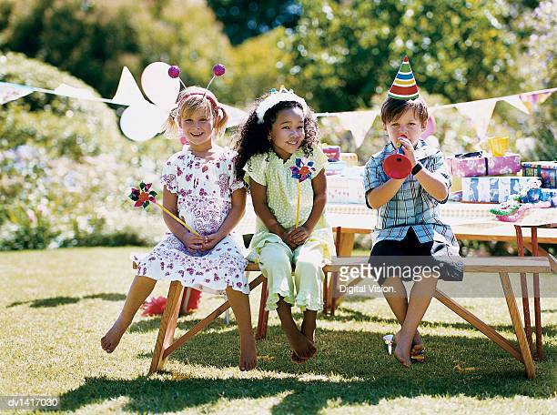 Two Girls and One Boy Sitting at a Garden Table at a Birthday Party