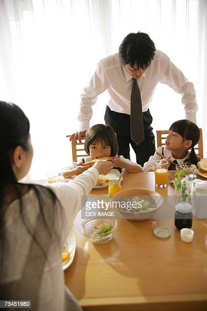 Two girls and their mother sitting at a dining table with their father standing behind them