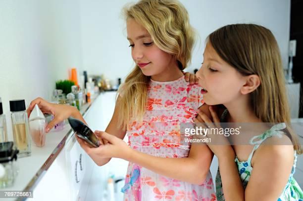 Two girls applying perfume in bathroom