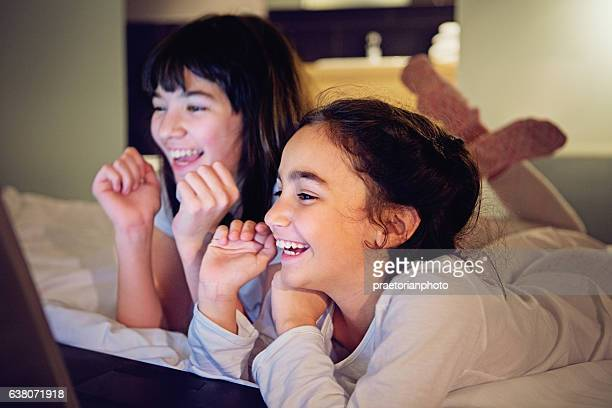 Two girls are looking in their laptop in the bed